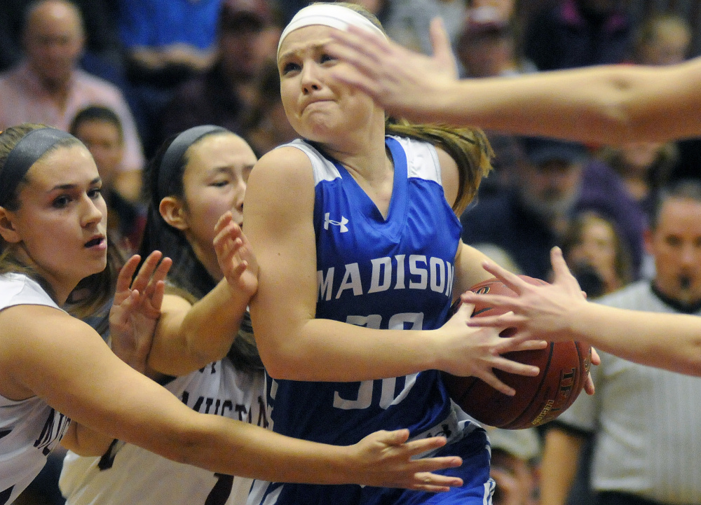 Madison's Madeline Wood tries to push through a tough Monmouth defense during a Mountain Valley Conference game Tuesday night in Monmouth.