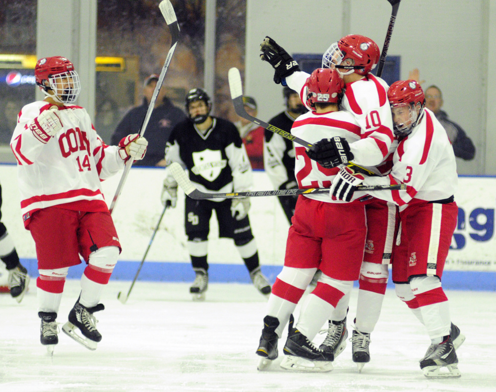 Cony's Riley Boivin (10) is congratulated by teammates Avery Pomerleau (14), Logan Leadbetter (25) and Connor Perry after Boivin scored a second period goal  to take a 1-0 over St. Dominic on Thursday  at Camden National Bank Ice Vault in Hallowell.