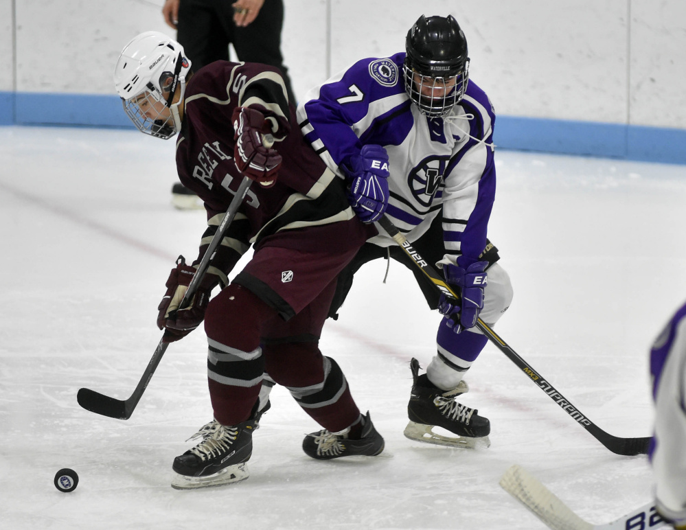 Greely High School's Andrew Eckhardt (5) looks to clear the puck as Waterville Senior High School's Nick Denis (7) tries to get the steal in the second period at Colby College on Thursday.