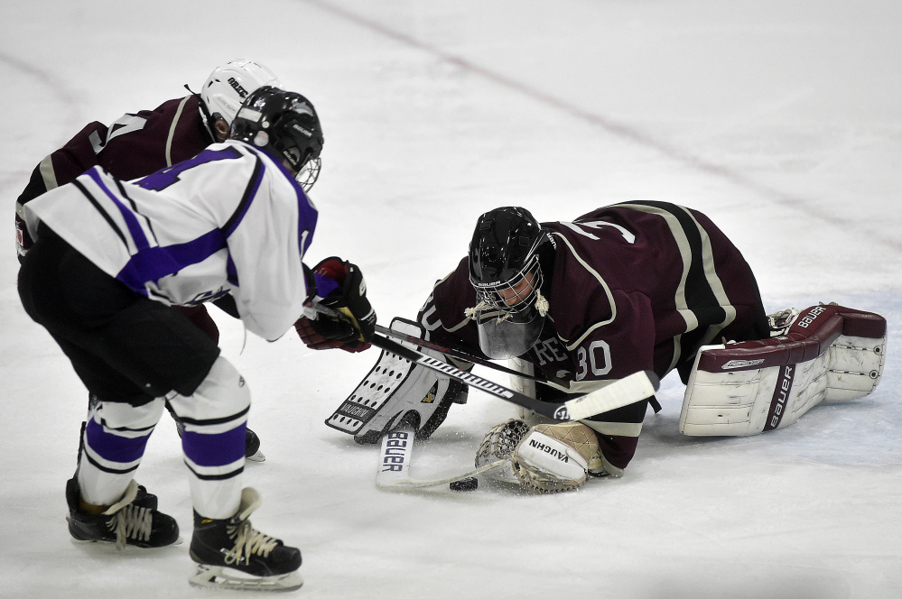 Greely High School goalie Joe McDonald (30) makes a save as Waterville Senior High School's Michael Oliveira (4) looks for the rebound at Colby College on Thursday.