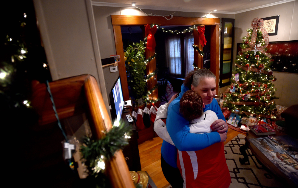 Carrie Harvey, left, is comforted by her friend Samantha Gladden, at Harvey's Waterville home on Thursday, as she talks about her brother Michael Bowles, who needs a kidney transplant.