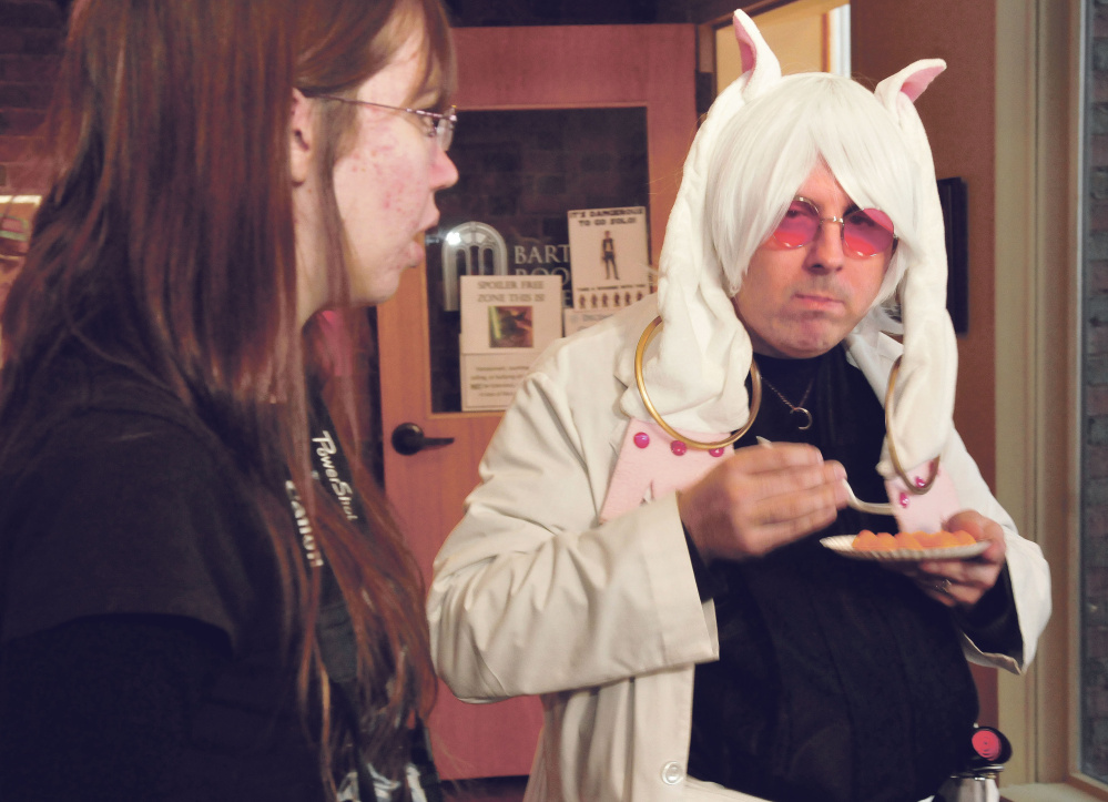 """Dressed as a """"Star Wars"""" Sith Lord and an anime figure called the Kyubey, Sean Duffy ponders a question from Sarah Taylor during a """"Star Wars"""" film party at the Waterville Public Library on Sunday."""