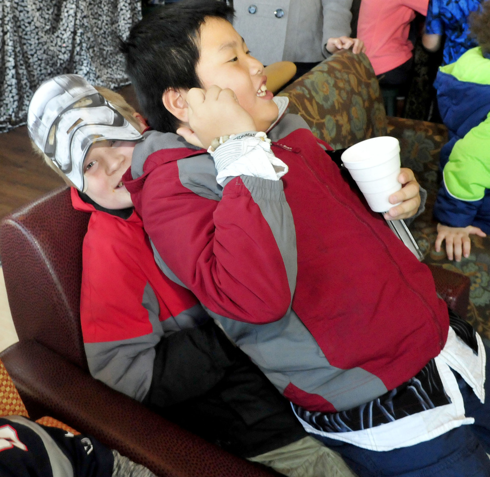 """Dressed as a """"Star Wars"""" storm trooper, Jadon Callahan gets squished by Evan Sotiriou during a """"Star Wars"""" movie party at the Waterville Public Library on Sunday."""