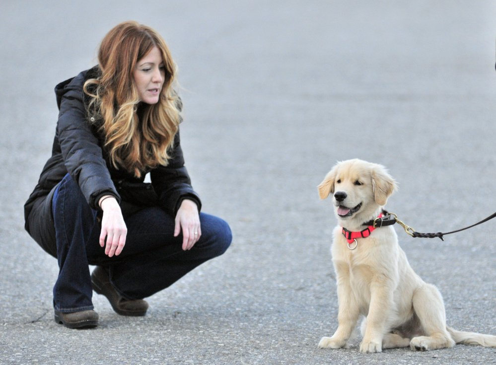AmyLou Craig, left, and her puppy Brewer on Nov. 24 in a parking lot near the Kennebec River Rail Trail in Augusta.