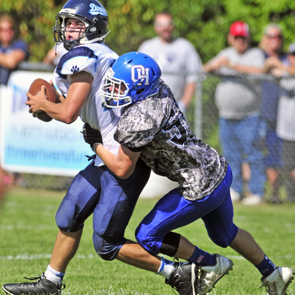 In this Sept. 12 photo, Dirigo quarterback Riley Robinson, left, gets sacked by Oak Hill defensive lineman Connor Elwell during third quarter of a game in Wales.
