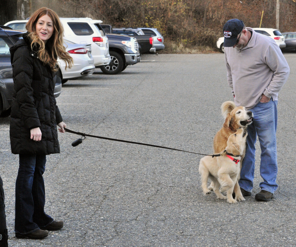 AmyLou Craig, left, and her puppy Brewer, stand with her father Lou Craig and his dog Miller on Nov. 24 in a parking lot near the Kennebec River Rail Trail in Augusta.