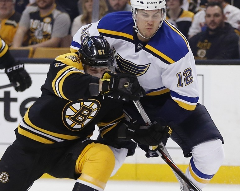 Boston's Ryan Spooner, left, and St. Louis' Jori Lehtera (12) battle for the puck during the first period Tuesday in Boston.