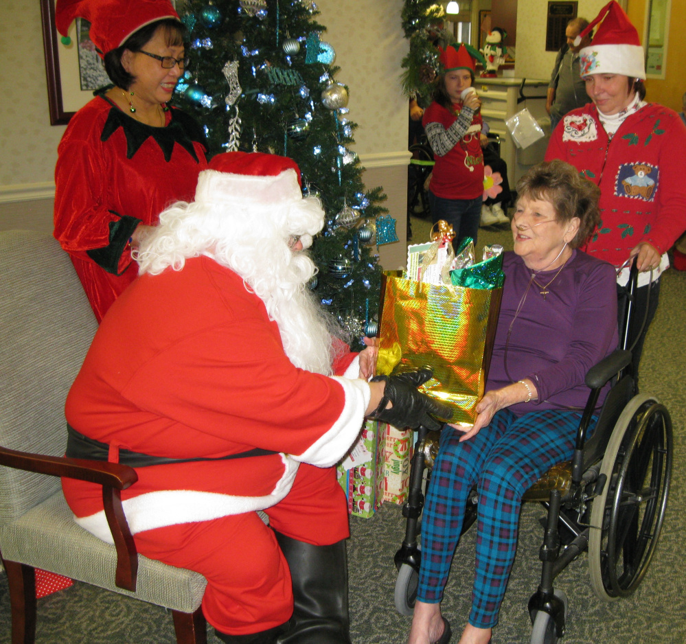 """Contributed photos Cedar Ridge resident Charlotte Spencer receives a gift from """"Santa Claus,"""" John Grohs, Transportation and """"Elf,"""" Activities Assistant Leni McCandless, and volunteer Theresa Drown"""