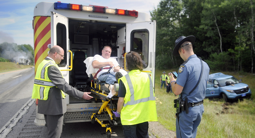 Maine State Police and medics load Trooper Greg Stevens into an ambulance July 30 after his cruiser was struck by a tractor-trailer in the northbound lanes of Interstate 295 in Richmond.