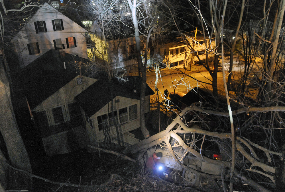 Ready Road Service wrecker operator Bill Maraglia hooks a cable on Friday to a vehicle that was lodged between trees on a banking between Crosby and Laurel streets in Augusta after a police chase. The vehicle's driver was arrested just before 11 p.m. after a pursuit by Augusta police that ended when he allegedly launched the vehicle over the steep embankment at the dead end of Crosby Street. Two wreckers from Ready Road Service were used to recover the vehicle.