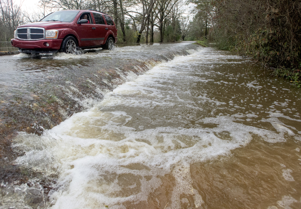 A vehicle drives along a flooded road in west Montgomery, Ala., on Christmas morning Friday. The line of springlike storms continued marching east Thursday, dumping torrential rain that flooded roads in Alabama and caused a mudslide in the mountains of Georgia.