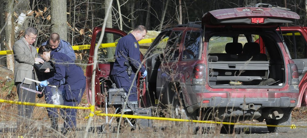 Staff photo by Andy Molloy Maine State Police evidence technicians examine the SUV containing the bodies of Augusta residents Eric Williams, 35, and Bonnie Royer, 26, discovered Friday on Sanford Road in Manchester.