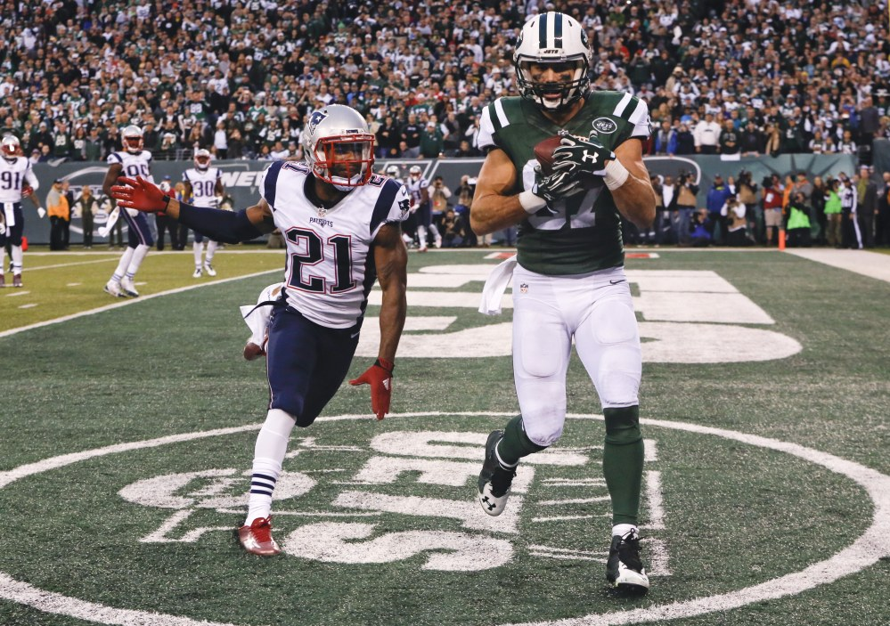 New York Jets wide receiver Eric Decker (87) catches a pass for a touchdown in front of New England Patriots' Malcolm Butler (21) during the overtime period of Sunday's game in East Rutherford, N.J. The Jets won 26-20.