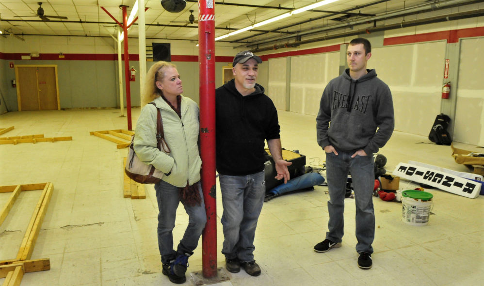 Staff photo by Dave Leaming In this Dec. 14 photo. Mike Leary, center, speaks about his O'Leary's Fitness boxing gym he is opening inside the former Marden's store building on College Avenue in Waterville. Beside him is his partner Kathleen Jones and trainer Matt Field.