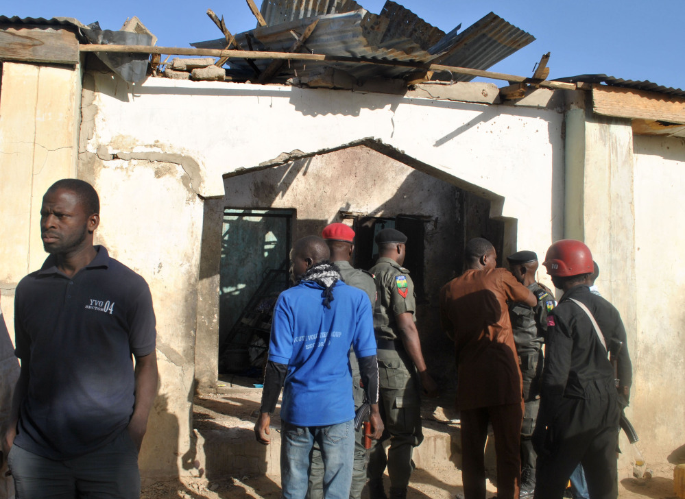 People gather at a damaged building following an attack by Boko Haram in Maiduguri, Nigeria Monday.