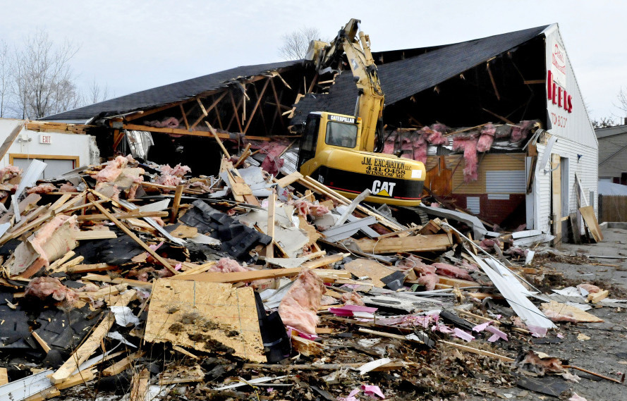 Jeremy Marcoux uses an excavator to demolish the former Weeks Auto Body business on Kennedy Memorial Drive in Waterville on Dec. 21.