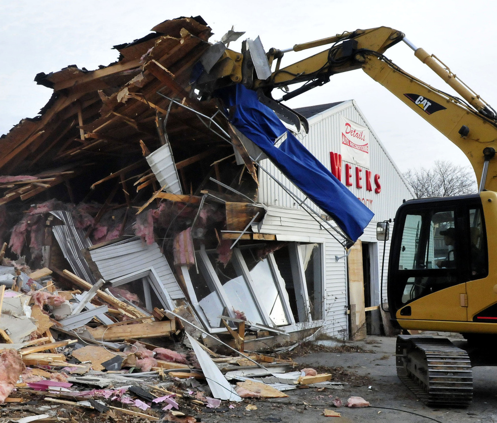 Jeremy Marcoux breaks down walls at the former Weeks Auto Body shop on Kennedy Memorial Drive in Waterville on Dec. 21.