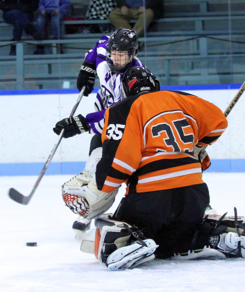 Waterville Senior High School's Andrew Roderigue tries to put a rebound past Winslow High School goalie Andrew Beals during first-period action at Colby College in Waterville on Monday. The teams played to a 4-4 overtime tie.
