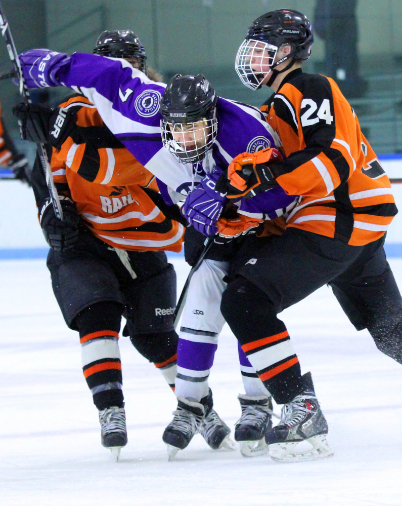 Waterville Senior High School's Nick Denis (7) gets checked by Winslow High School's David Selwood during first-period action at Colby College in Waterville on Monday. The teams played to a 4-4 overtime tie.