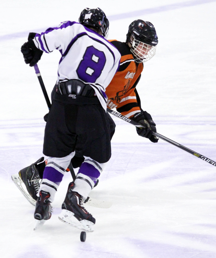 Winlsow High School's Jimmy Fowler get checked off the puck by Waterville Senior High School's Justin Wentworth during second-period action at Colby College in Waterville on Monday. The teams played to a 4-4 overtime tie.