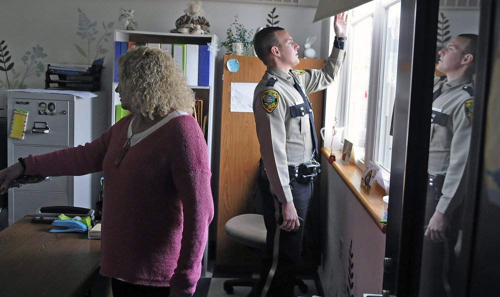 Deputy Aaron Moody and principal Christine Lajoie-Cameron examine a window Monday that a thief broke to gain entry to the Carrie Ricker School in Litchfield.