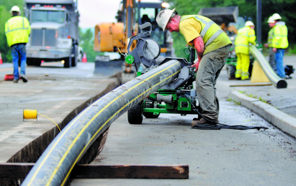 Workers with Bowdoin Excavation lay gas pipes in Augusta for Maine Natural Gas in this 2013 file photo.