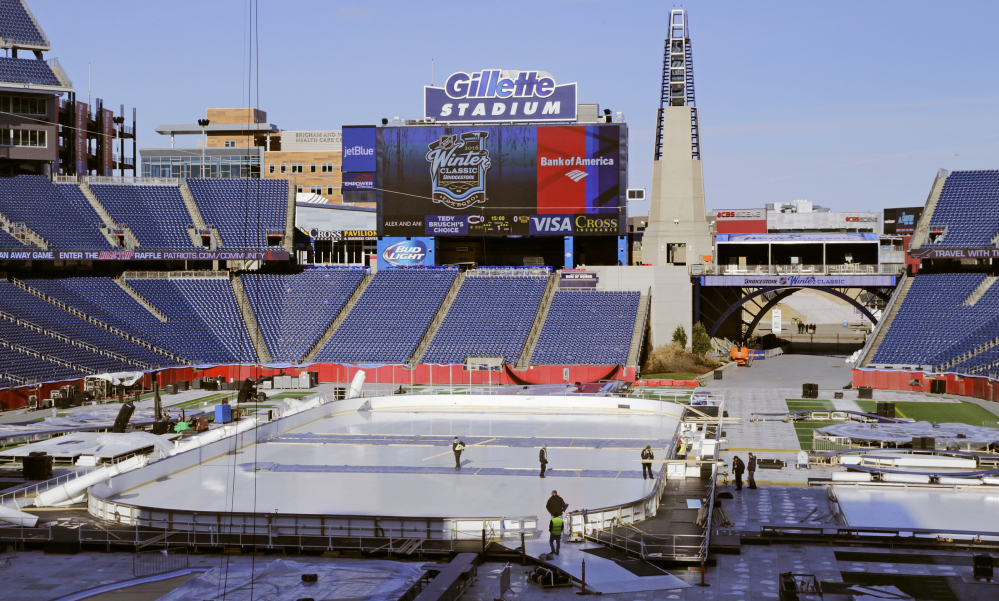 Workers prepare the Winter Classic hockey rink on the football field of Gillette Stadium in Foxborough, Mass. The Montreal Canadiens face the Boston Bruins in the New Year's Day hockey game in the home of the New England Patriots.