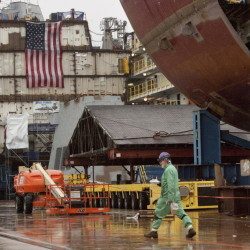 BATH, ME - DECEMBER 10: A shipbuilder walks in the yard, with partial ship assemblies behind him, at Bath Iron Works in Bath on Wednesday, December 10, 2014. (Photo by Carl D. Walsh/Staff Photographer)