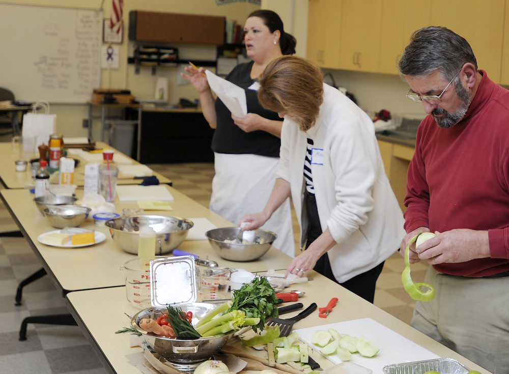 """Adult education students Mary Murphy and Pete Blunda, both from Gorham, help prep the ingredients for an apple crisp recipe in a """"comfort foods"""" cooking class taught by JoAnne Wood at Gorham Middle School."""
