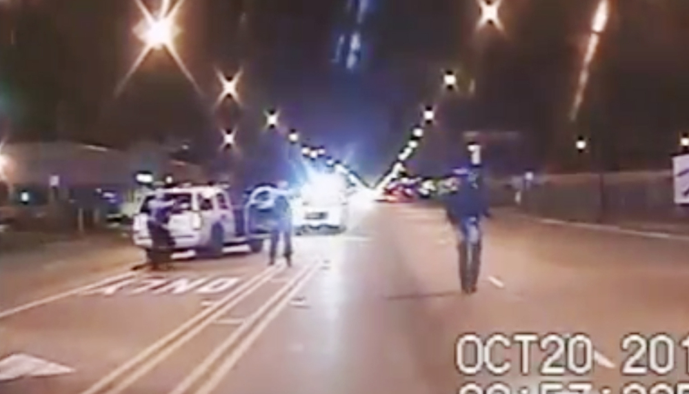 In this Oct. 20, 2014 frame from dash-cam video, Laquan McDonald, right, walks down the street moments before being shot by police officer Jason Van Dyke in Chicago.