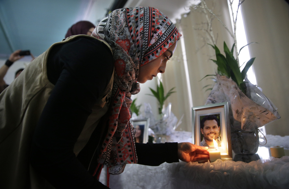 Khadija Zadeh lights candles next to the framed photos of 14 victims killed in Wednesday's shooting rampage before the start of Sunday's memorial service at the Islamic Community Center of Redlands in Loma Linda, Calif.