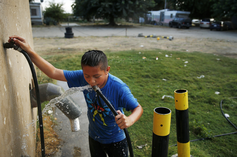 Carlos Velasquez, 9, drinks well water from a hose at a trailer park near Fresno, Calif.