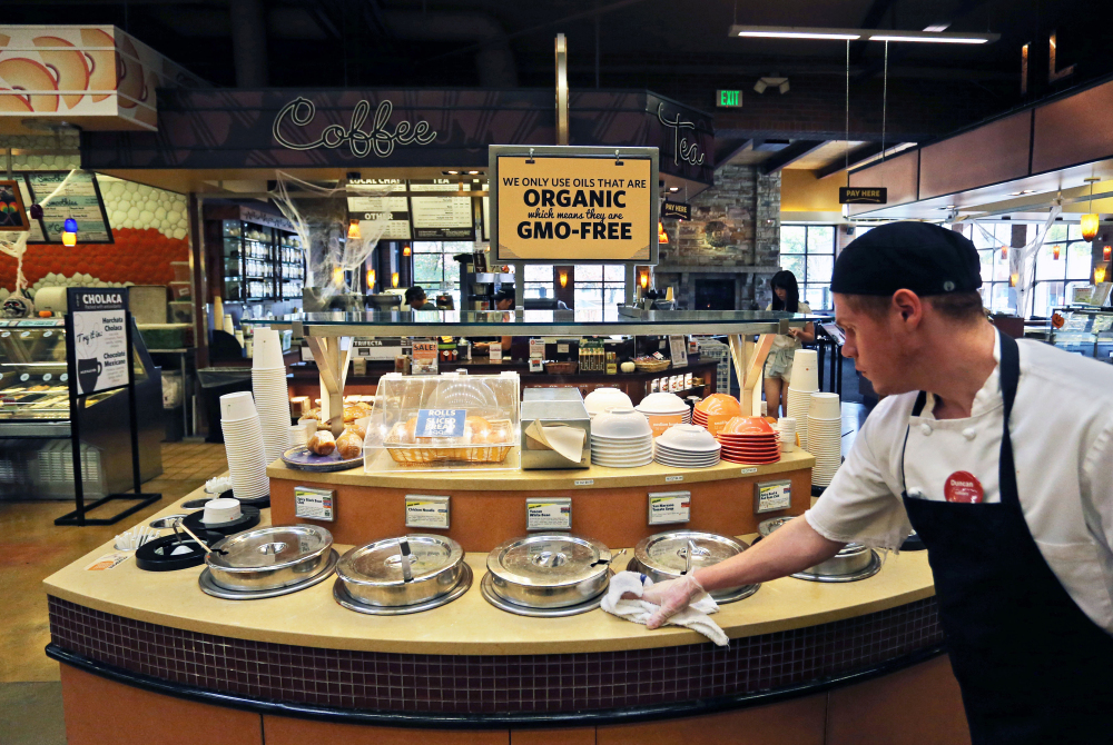 A grocery store employee wipes down a soup bar with a display informing customers of organic, GMO-free oils, in Boulder, Colo.