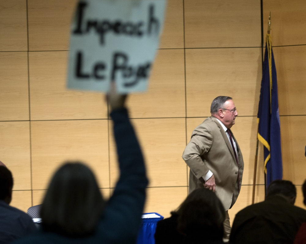 An audience member holds up a sign as Gov. LePage leaves the room after his town hall tour event at USM. Derek Davis/Staff Photographer