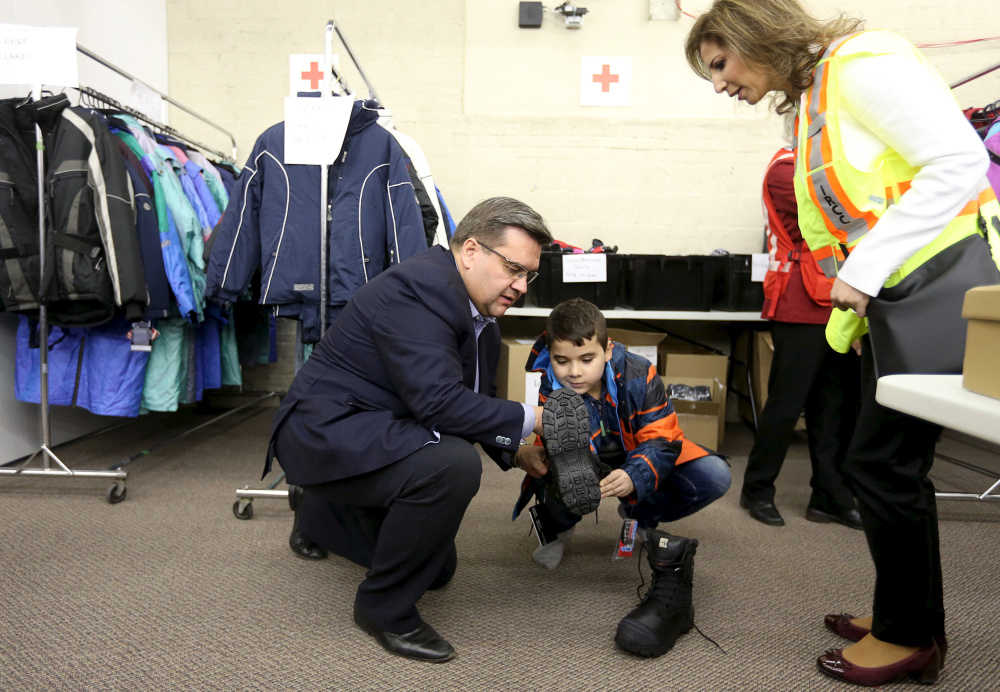 Montreal Mayor Denis Coderre helps Syrian boy Raffi Der Kaspar, 10, try on boots at the Welcome Centre in Montreal after a second military airlift of refugees arrived Saturday. Canada expects to resettle 10,000 refugees by year's end.