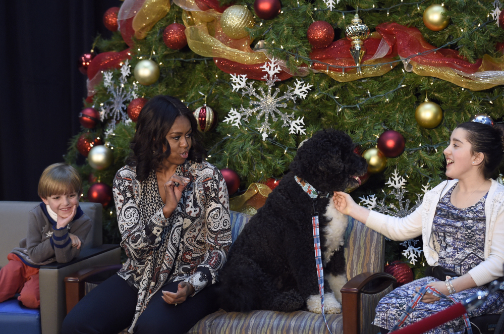 """First lady Michelle Obama sits with Stephen Orzechowski and Luna Fera, wo pets Bo, as she answers questions after reading """"Twas the Night Before Christmas"""" to a group of children at the Children's National Health System in Washington on Monday."""