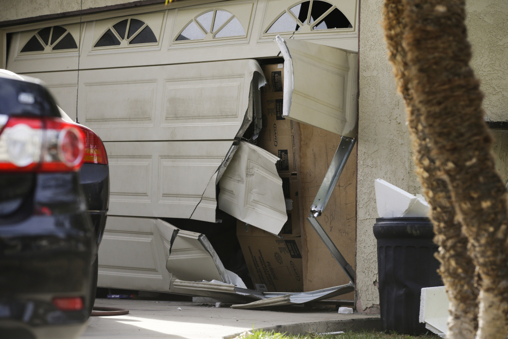 A garage door of Enrique Marquez's home is broken Dec. 9 after an FBI raid in Riverside, Calif. Marquez, a former security guard who bought the assault rifles used by his friend in the San Bernardino massacre, was charged Thursday.