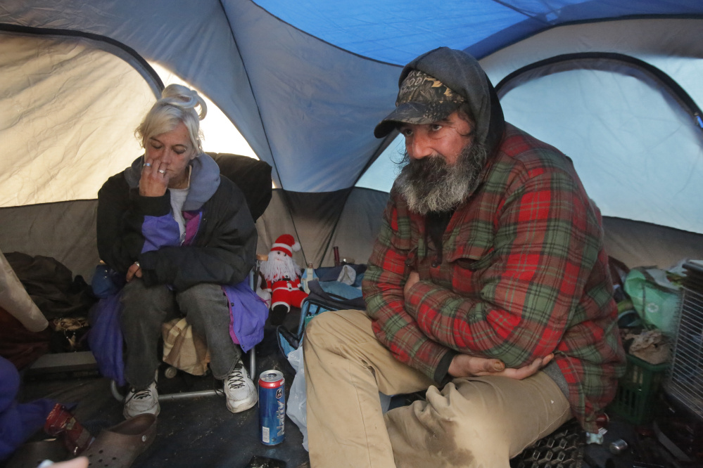 """Sherri Ferrier and Jamey Wade spend time on a rainy Thursday in Ferrier's propane-heated tent in the woods on the outskirts of Portland, where Wade also has a tent. Ferrier was not displaced by the state's brush-clearing project along Interstate 295 but says she has had her camps torn down in the past. """"It's sad because they're taking everything away from us,"""" she said."""