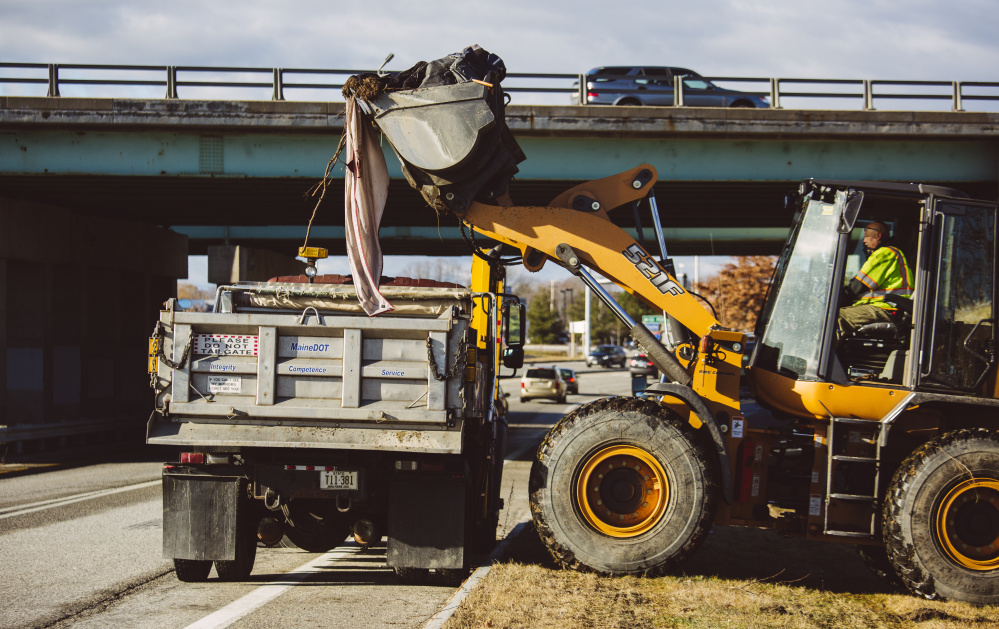 State workers remove the belongings of at least one homeless person who was living in a camp near the Exit 5 off-ramp on Interstate 295. One-and-a-half truckloads of materials were removed in all.