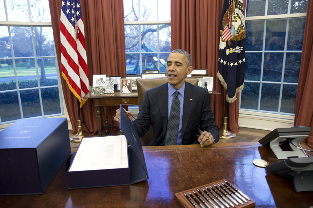 President Obama closes the folio box after signing the budget in the Oval Office of the White House on Friday in Washington.