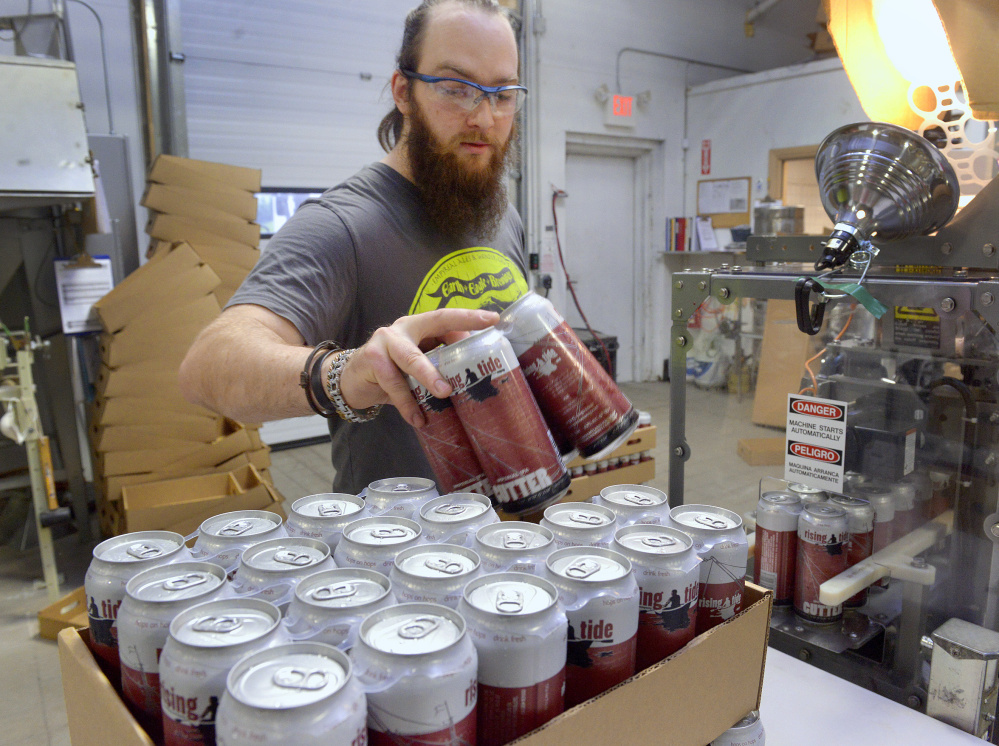 A booming microbrewery industry has led to a shortage of the humble beer can. That's left Maine brewers scrambling to plan for the busy summer   season. Rising Tide Brewery employee Eric Altman loads four-packs of beer into cases during a canning run at the Portland brewery Monday. John Ewing/Staff Photographer