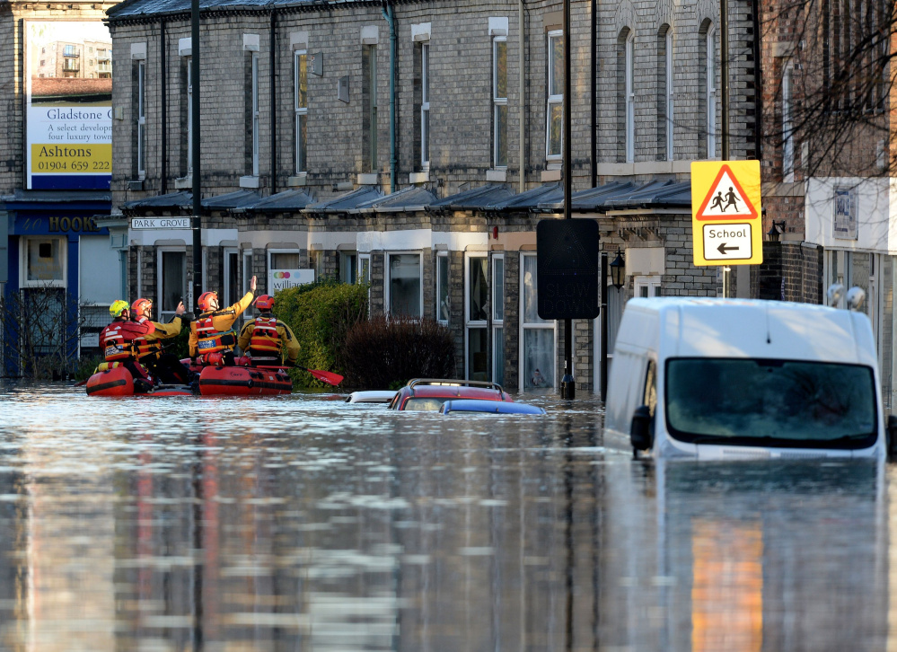 Members of a mountain rescue team check on properties after the rivers Foss and Ouse burst their banks, in York, England, on Sunday. Hundreds were forced to evacuate.