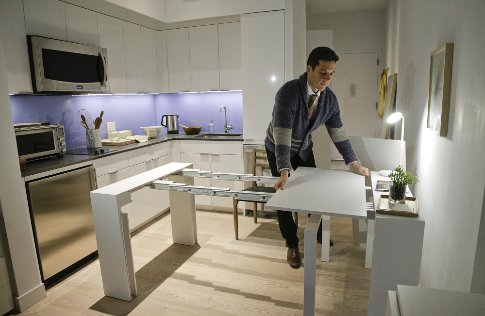 Stage 3 Properties co-founder Christopher Bledsoe demonstrates a desk that expands into a dining table inside one of the mini-apartments at Carmel Place in New York.