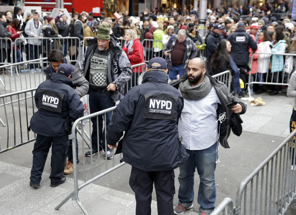Pedestrians wait to be searched as they enter Times Square in New York on Thursday. About 1 million people are expected to attend festivities on Times Square, along with nearly 6,000 New York City police officers, including members of a specialized counterterrorism unit.