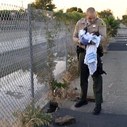Deputy Adam Collette holds an infant girl found abandoned under asphalt and rubble near a bike path in Compton, Calif., on Friday, in this photo provided by the Los Angeles County Sheriff's Department.