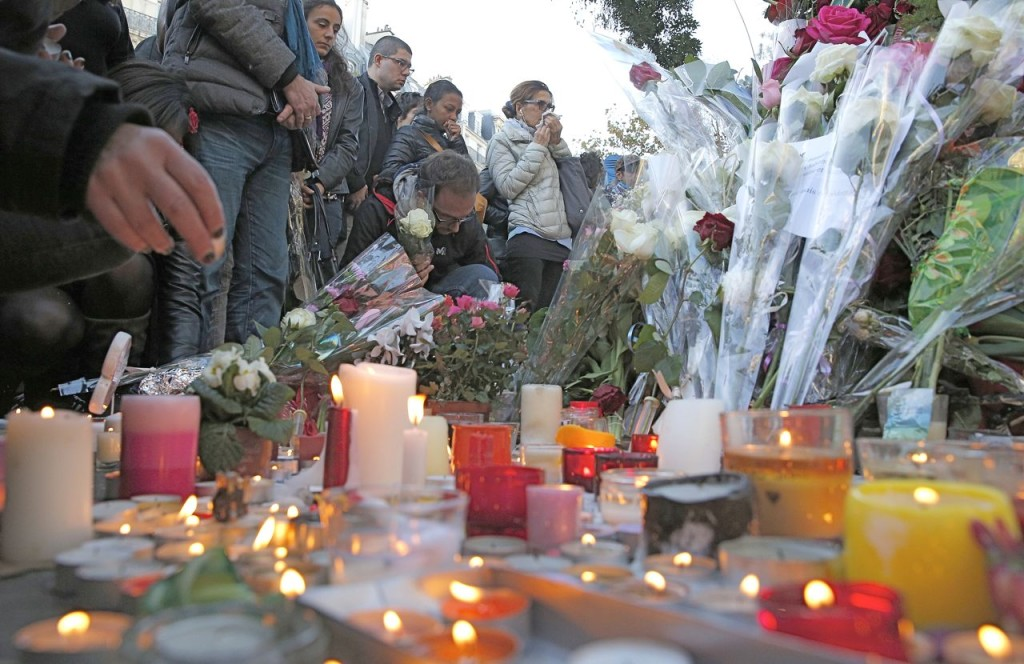Mourners place flowers and light candles outside the Bataclan concert hall in Paris on Nov. 15. Ninety people died at the concert hall after three gunmen stormed a rock concert by the California band, Eagles of Death Metal. The Associated Press
