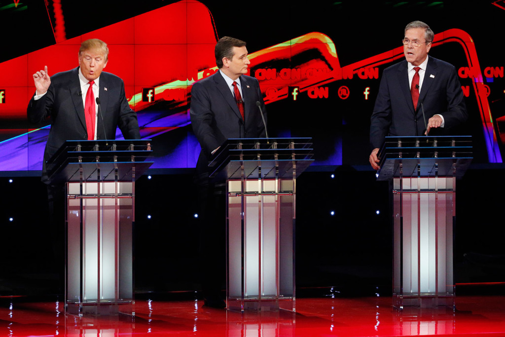 Donald Trump, left, and Jeb Bush, right, speak as Ted Cruz looks on during Tuesday night's Republican presidential debate in Las Vegas. Bush, needing a strong debate performance, was aggressive in seeking to discredit Trump. The Associated Press
