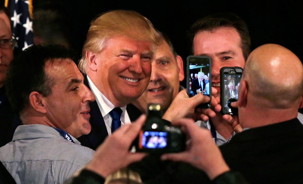 Donald Trump poses for a photograph with supporters after being endorsed at a regional police union meeting in Portsmouth, N.H., on Thursday evening. The Associated Press