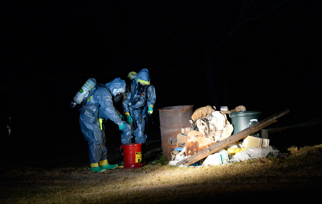 """Members of the Maine Drug Enforcement Agency go through a burn pile on the property of 125 Old Thompson Road in Buxton. They said they discovered three """"one-pot"""" bottles used to make methamphetamine in the pile Tuesday."""