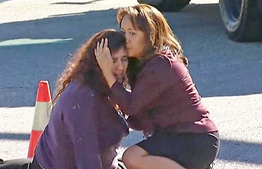 Two women comfort each other near the scene of the mass shooting outside a social services center in San Bernardino, Calif. KNBC via AP